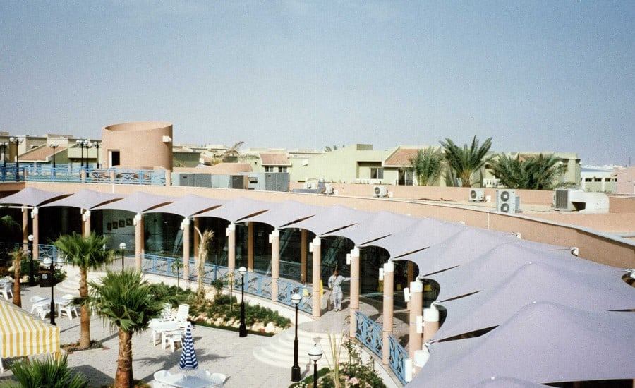 Tensile fabric canopies surrounding swimming pool
