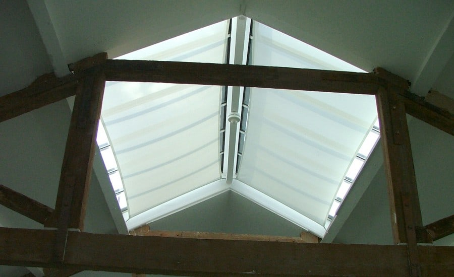 Tensile fabric screens under roof lights