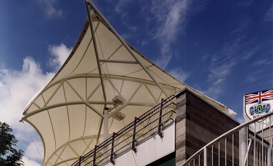 Dramatic wing like tensile fabric roof over silverstone clubhouse